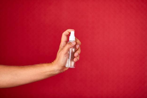 Mężczyźni Ręka Trzymająca Spray Odkażający Na Czerwonym Tle Studia, Sprzęt Ochronny Na Koronawirusa, Antyseptyczny Spray Odkażający, Dezynfekcja, Antyseptyczna Ochrona Rąk Podczas Pandemii Covid-19 Premium Zdjęcia