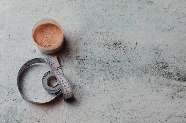 Miarka lub łyżka białka serwatkowego o widocznej fakturze. smak czekolady. skopiuj miejsce Premium Zdjęcia