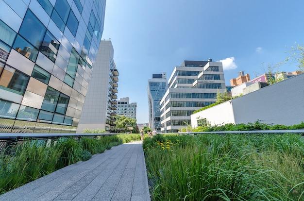 Miasto Nowy Jork, Lipiec - 22: Ludzie Chodzą Wzdłuż Wysokiej Linii Parka Na Lipu 22, 2014. Wysoka Linia Jest Popularnym Liniowym Parkiem Budującym Na Podwyższonej Poprzedniej Nowy Jork Linii Kolejowej środkowej Ostrodze W Manhattan. Premium Zdjęcia
