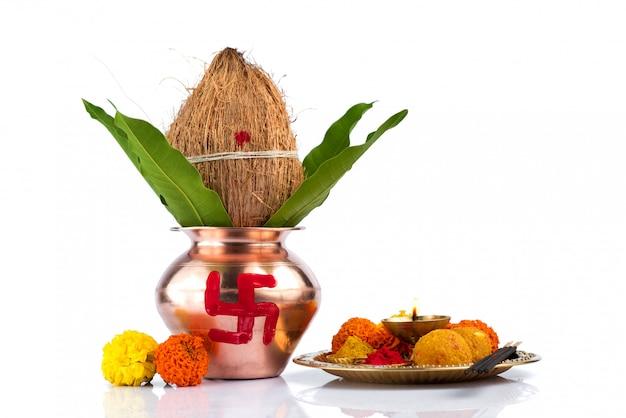 Miedź kalash z liśćmi kokosa i mango oraz pooja thali z diya, kumkum i słodyczami z kwiatową dekoracją. niezbędny w hinduskiej pudży. Premium Zdjęcia