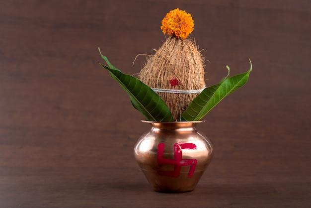 Miedziany kalash z liściem kokosa i mango z kwiatową dekoracją na drewnie. Premium Zdjęcia