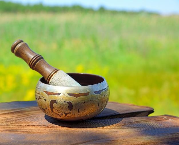 Miedziany Tybetański śpiewu Puchar Na Brown Drewnianym Tle, Zamazany Tło Premium Zdjęcia