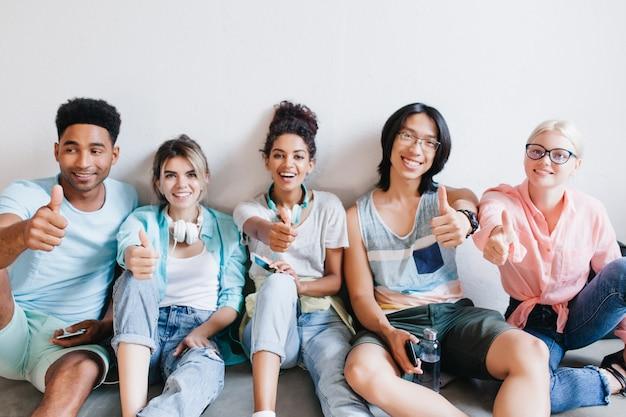 Międzynarodowi Studenci Siedzą Na Podłodze I Pozują Z Kciukiem Do Góry. Szczęśliwi Przyjaciele Ze Studiów W Stylowych Ubraniach Bawią Się W Kampusie Po Zajęciach. Darmowe Zdjęcia