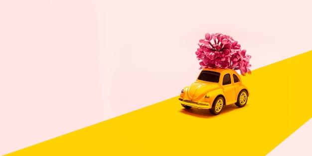 Międzynarodowy dzień szczęśliwych kobiet. zabawkarski żółty samochód z lilą kwiat gałąź na różowym tle z miejscem dla teksta. Premium Zdjęcia