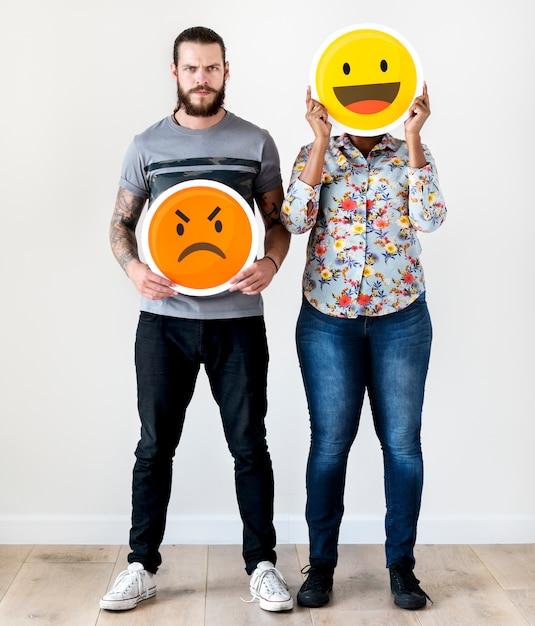 Międzyrasowa para trzyma ekspresyjnego emoticon twarzy wyraz twarzy marszczy brwi i uśmiech relacje Premium Zdjęcia