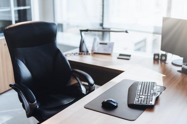 Miejsce pracy biznesmena: komputer, drewniany stół i krzesło w szafce Premium Zdjęcia