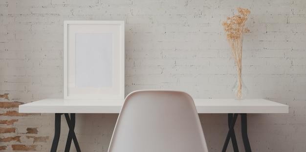 Miejsce pracy na poddaszu z białym drewnianym biurkiem, ramą makiety i wazonem w vintage ceglanym murze Premium Zdjęcia