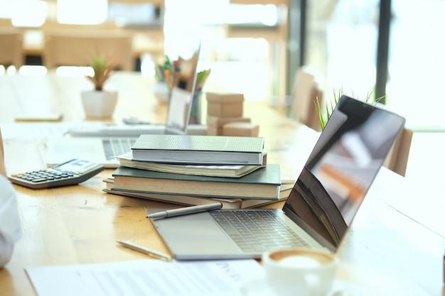 Miejsce pracy z laptopem i książkami na drewnianym stole z rannym światłem. Premium Zdjęcia