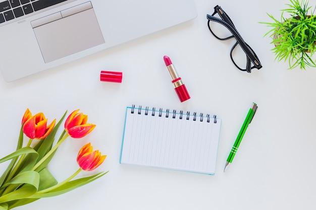 Miejsce pracy z notatnikiem i laptopem z tulipanem i pomadą Darmowe Zdjęcia