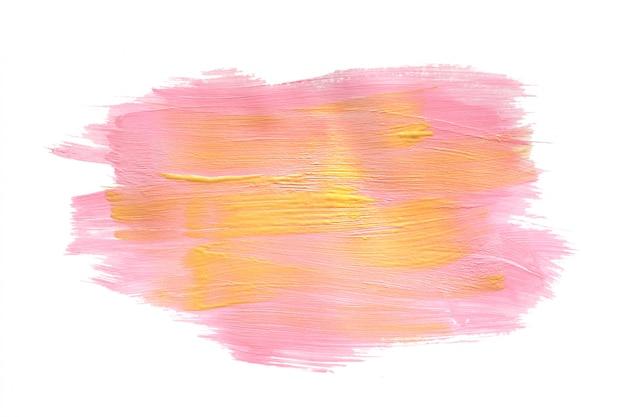 Miejsce rozmazanej farby akrylowej w kolorze różowego i żółtego złota. na białym tle Premium Zdjęcia