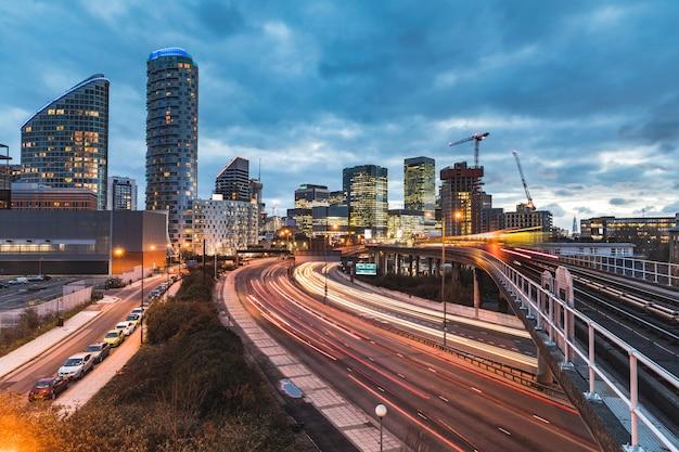 Miejski widok z drapaczami chmur, zamazanymi pociągami i światłami szlaków Premium Zdjęcia