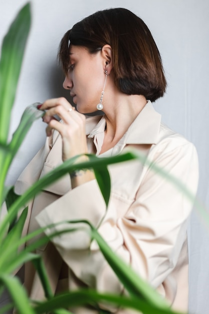 Miękki, Wewnętrzny Portret Kaukaskiej Delikatnej Kobiety W Beżowym Garniturze Bez Stanika, Pozująca Za Palmą Tropikalną Rośliną, Szary. Darmowe Zdjęcia