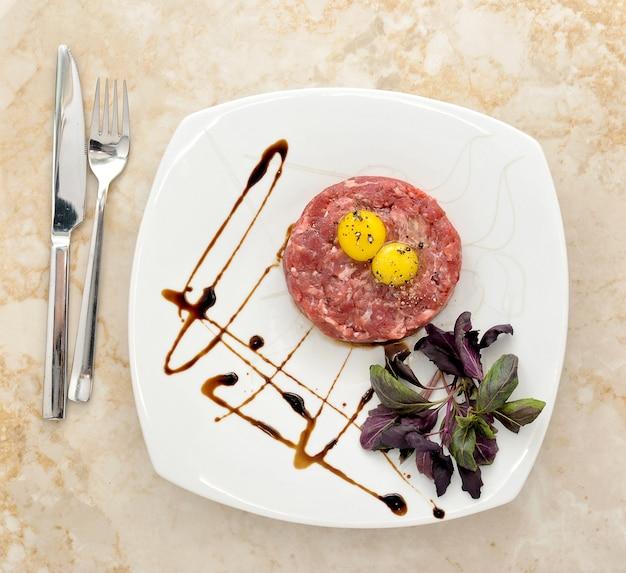 Mielona wołowina i surowe jajko z ziołami i przyprawami Premium Zdjęcia
