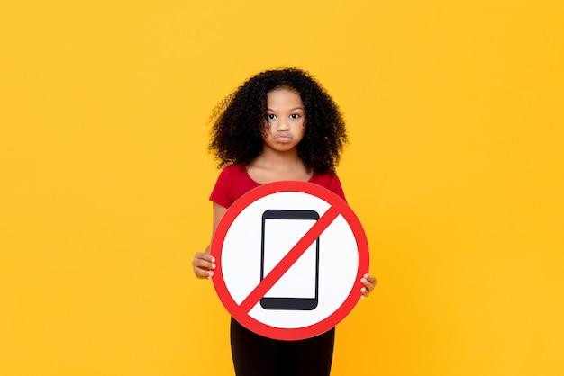 Mieszana Biegowa Afrykańska Dziewczyna Pokazuje żadny Znak Użycia Telefonu Komórkowego Odizolowywającego Na Kolorowej Kolor żółty ścianie Premium Zdjęcia