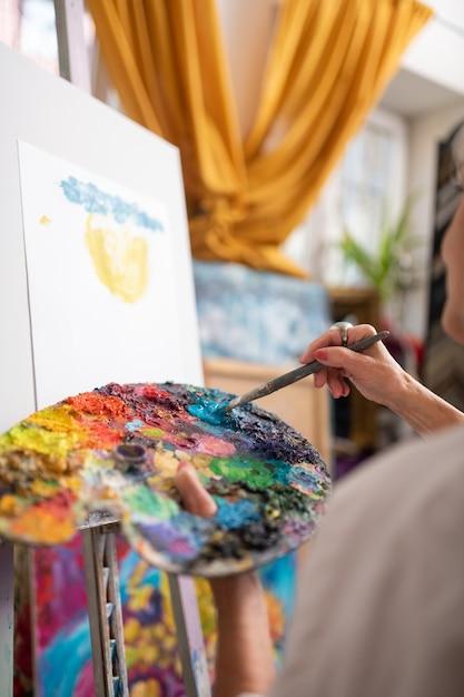 Mieszanie Kolorowego Gwaszu. Utalentowana Kobieta Trzyma Paletę Kolorów Mieszającą Kolorowy Gwasz I Malarstwo Premium Zdjęcia