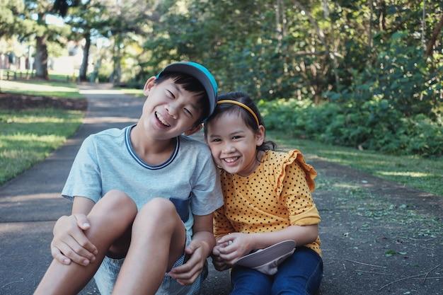 Mieszany azjatycki młodszy brat i siostra na zewnątrz, Premium Zdjęcia