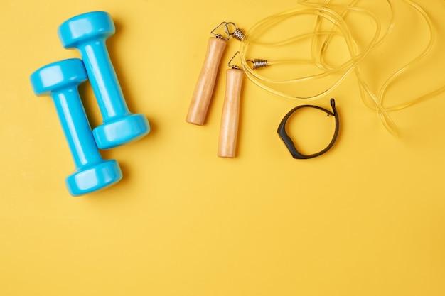 Mieszkanie leżał skład niebieskie hantle, skakanka i fitness tracker na żółtym tle z miejsca na kopię Premium Zdjęcia