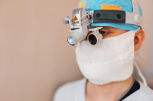 Mikrochirurg W Białej Masce W Specjalnej Odzieży Medycznej I Okularach Z Lupą Lornetkową Na Sali Operacyjnej. Chirurg Przeprowadza Operację. Sprzęt Szpitalny Premium Zdjęcia