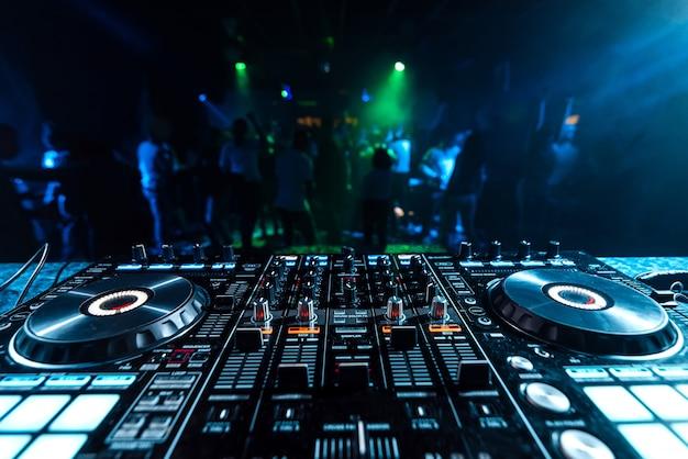 Mikser muzyczny dj w kabinie w klubie nocnym na niewyraźnym tle tańczących ludzi Premium Zdjęcia