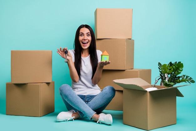 Miła Atrakcyjna Ekstatyczna Wesoła Wesoła Dziewczyna Siedzi W Pozycji Lotosu, Trzymając W Ręku Postać Domu Premium Zdjęcia