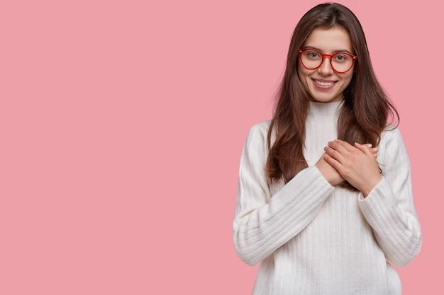 Miła Czuła Dziewczyna Przyciska Dłonie Do Serca W Wdzięcznym I Wzruszonym Geście, Ma Przyjemny Uśmiech Darmowe Zdjęcia