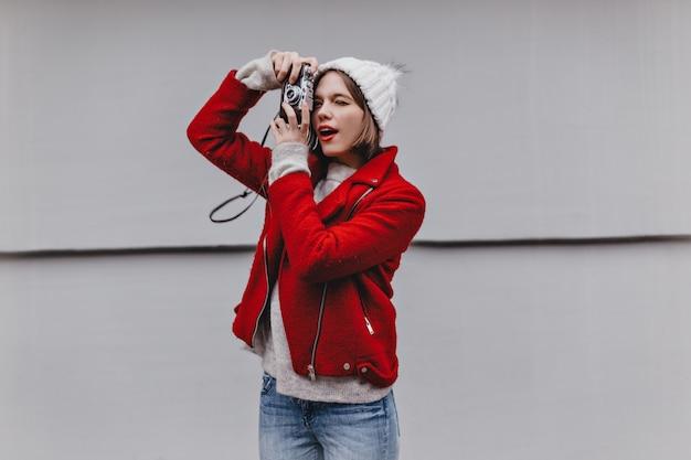 Miła Dziewczyna Z Czerwoną Szminką Fotografuje Retro Aparat. Portret Kobiety W Ciepły Krótki Płaszcz, Dżinsy I Czapka Na Szarym Tle. Darmowe Zdjęcia
