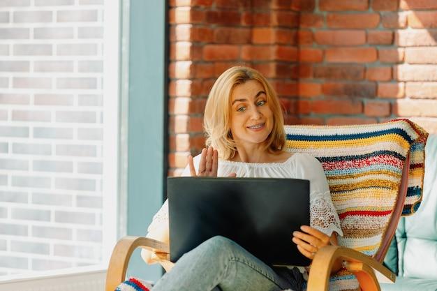 Miła Kobieta Uśmiecha Się I Macha Ręką Przed Laptopem. Wideokonferencja W Wygodnym Fotelu Bujanym. Premium Zdjęcia