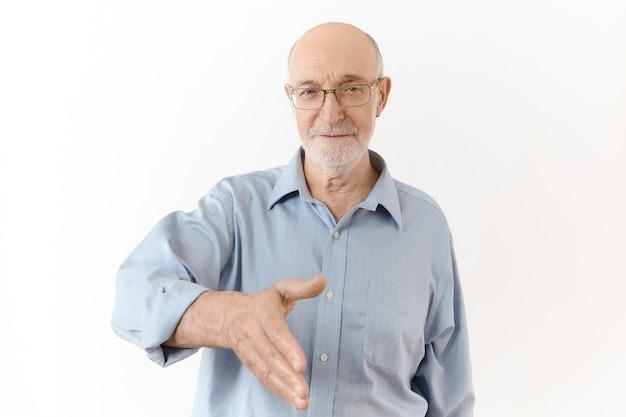 Miło Cię Poznać. Pojedyncze Ujęcie Eleganckiego, Formalnie Ubranego Starszego Mężczyzny Z Białą Brodą, Wyciągając Dłoń, Zamierzając Uścisnąć Dłoń Na Znak Powitania. Język Ciała, Znaki I Gesty Darmowe Zdjęcia