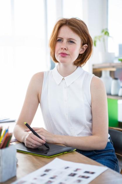 Miło hipster interesu siedzi przy biurku z cyfrowym tabletem rysowania Premium Zdjęcia