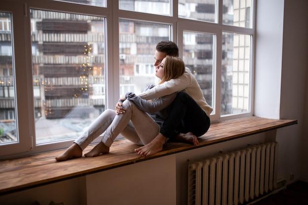 Miłości Para Siedzi Razem I Spójrz W Okno. Walentynki. Premium Zdjęcia