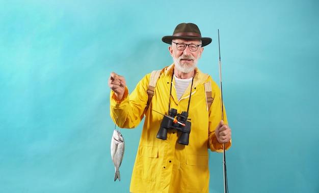 Miły Starzec Szczęśliwy Rybak, Trzymający Wędkę Z Połowem, Złowione Ryby, Zbliżenie Rybaka Na Odosobnionej ścianie Premium Zdjęcia