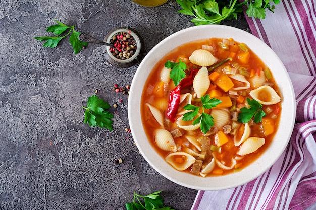 Minestrone, Włoska Zupa Jarzynowa Z Makaronem Na Stole. Wegańskie Jedzenie. Widok Z Góry Premium Zdjęcia