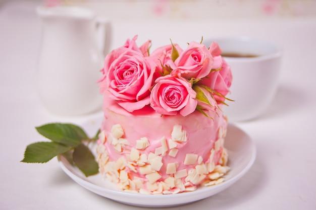 Mini Małe Ciasto Z Różową Polewą, Piękne Róże, Filiżanka Kawy, Pudełko Na Białym Stole. Premium Zdjęcia