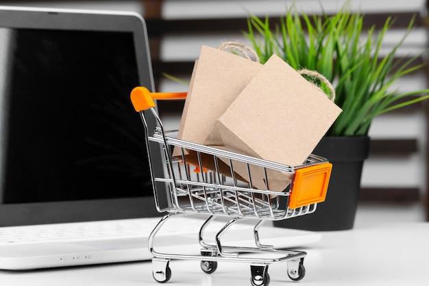 Mini wózek na zakupy i laptop na biurku Premium Zdjęcia