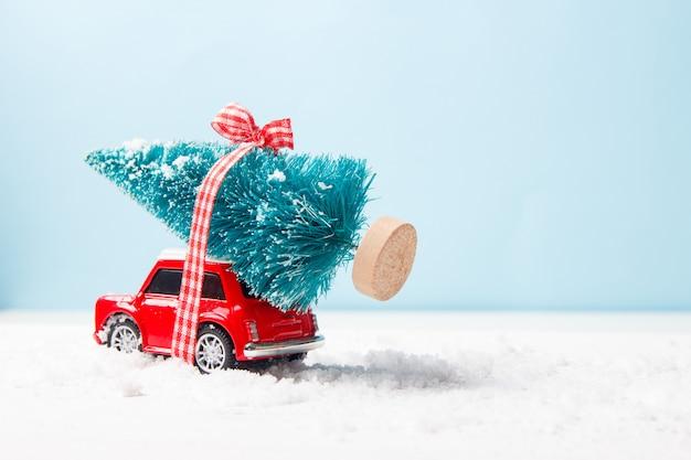 Miniaturowa czerwona samochód zabawka dostarcza choinki na błękicie Premium Zdjęcia