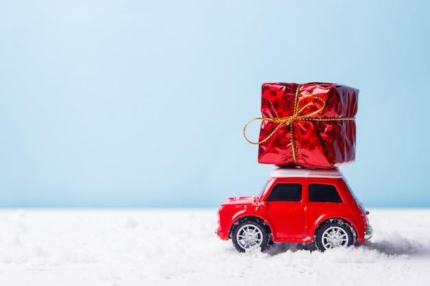 Miniaturowa czerwona zabawka samochodowa dostarczająca pudełko na niebiesko Premium Zdjęcia