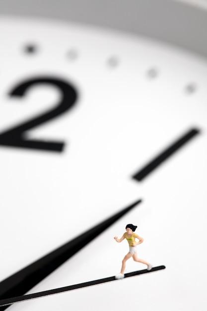 Miniaturowa dziewczyna z zegarem z drugiej ręki Premium Zdjęcia