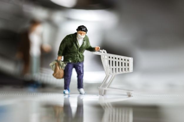 Miniaturowa Figurka Noszenia Maski Kupujący Biznes Popycha Wózek Na Papierowy Indeks Ze Stetoskopem Premium Zdjęcia