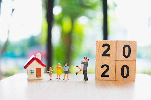 Miniaturowa Stojąca Rodzina Z Mini Domkiem I 2020 Drewnianymi Klockami Premium Zdjęcia