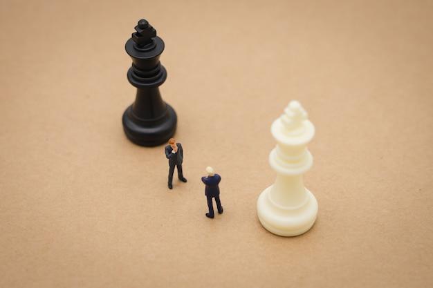 Miniaturowe 2 biznesmenów stojących z powrotem negocjowanie w biznesie. Premium Zdjęcia