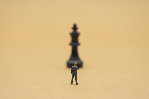 Miniaturowe biznesmenów stojących analiza szachowa komunikuj o biznesie Premium Zdjęcia