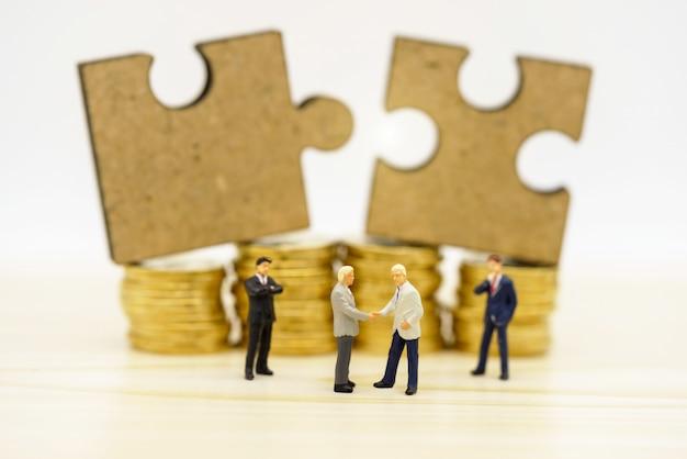 Miniaturowe Osoby: Uścisk Dłoni Biznesmenów Z Układanką Na Stosie Monet. Finanse Premium Zdjęcia