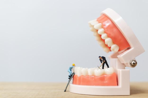 Miniaturowe osoby: zespół pracowników naprawiający ząb Premium Zdjęcia