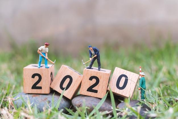 Miniaturowe Osoby, Zespół Pracowników Tworzą Drewniany Blok O Numerze 2020 Premium Zdjęcia