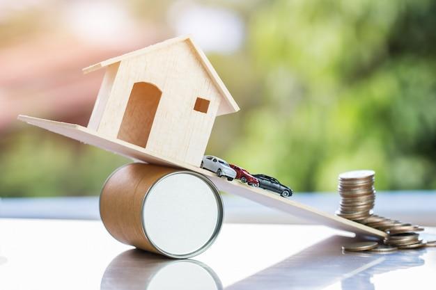 Miniaturowe samochody, dom na desce spadają z drogi. to jak nieformalne finansowanie kredytów dłużnych lub awaria własności spowodowana nadprodukcją Premium Zdjęcia