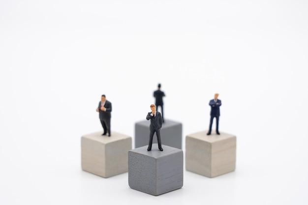 Miniaturowi 4 ludzie biznesmenów stoi na drewnianej sześcian inwestorskiej analizie Premium Zdjęcia