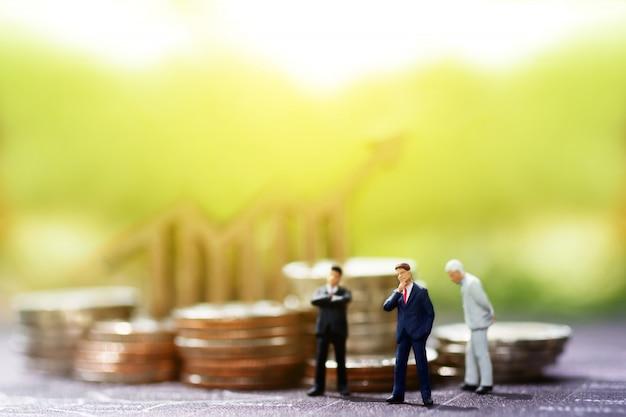 Miniaturowi biznesmeni stoi z wykresu i monet stosem. Premium Zdjęcia