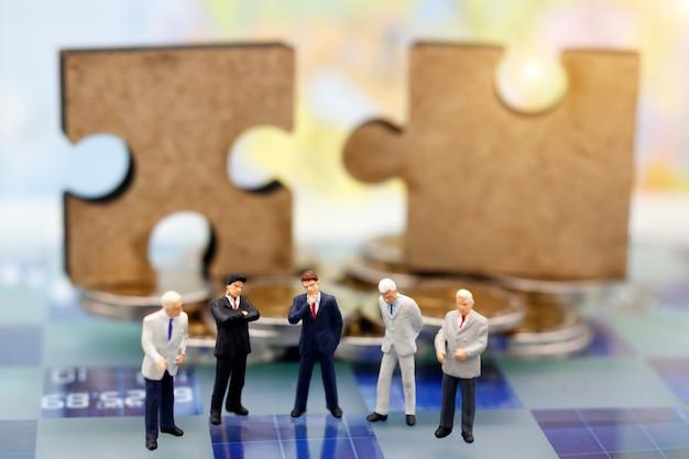 Miniaturowi Ludzie, Biznesmen Myślą Z Układanki Na Stosie Monet. Premium Zdjęcia