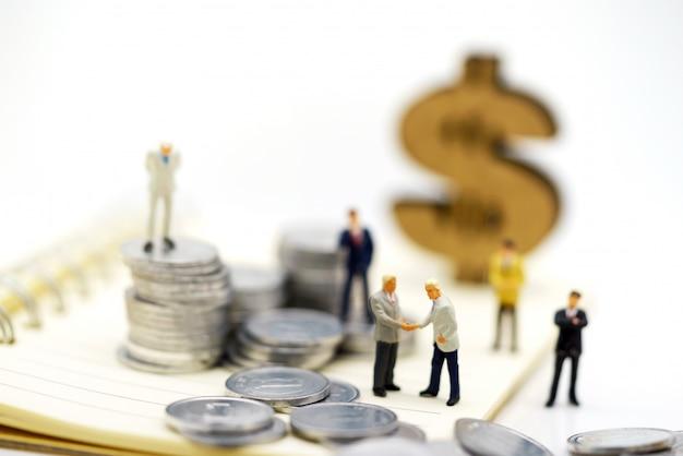 Miniaturowi ludzie, biznesmeni stoi z monety stertą, finanse i inwestyci pojęcie. Premium Zdjęcia