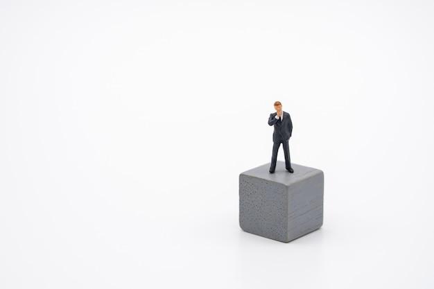 Miniaturowi ludzie biznesmenów stoi na drewnianej sześcian inwestorskiej analizie Premium Zdjęcia